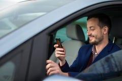 Όμορφος νεαρός άνδρας που εξετάζει το κινητό τηλέφωνο του Στοκ Φωτογραφία