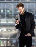 Όμορφος νεαρός άνδρας που εξετάζει το κινητό τηλεφωνικό μήνυμα κειμένου Στοκ φωτογραφίες με δικαίωμα ελεύθερης χρήσης