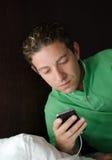 Όμορφος νεαρός άνδρας που εξετάζει το τηλέφωνο κυττάρων τη νύχτα στο κρεβάτι Στοκ Εικόνες