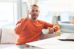 Όμορφος νεαρός άνδρας που εργάζεται με το σημειωματάριο, που μιλά στο τηλέφωνο, χαμόγελο, που εξετάζει τη κάμερα, απολαμβάνοντας  Στοκ εικόνα με δικαίωμα ελεύθερης χρήσης