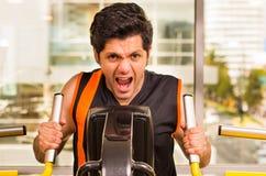 Όμορφος νεαρός άνδρας που εργάζεται στη μηχανή ικανότητας στη γυμναστική και που κραυγάζει ταυτόχρονα Στοκ Εικόνες