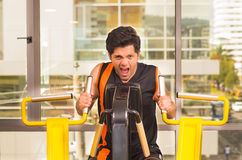 Όμορφος νεαρός άνδρας που εργάζεται στη μηχανή ικανότητας στη γυμναστική και που κραυγάζει ταυτόχρονα Στοκ Εικόνα