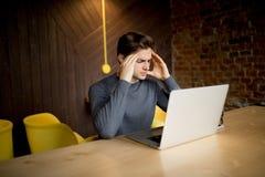 Όμορφος νεαρός άνδρας που εργάζεται στο lap-top με το λυπημένο πρόσωπο ή τον επικεφαλής πόνο που λειτουργεί στο lap-top Στοκ φωτογραφία με δικαίωμα ελεύθερης χρήσης