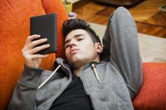 Όμορφος νεαρός άνδρας που διαβάζει στο σπίτι με το ebook Στοκ Εικόνα