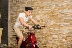 Όμορφος νεαρός άνδρας που κάνει την περιστροφή στο ποδήλατο στοκ εικόνες