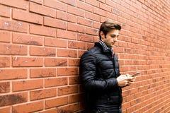 Όμορφος νεαρός άνδρας που κρατά το κινητό τηλέφωνο και που εξετάζει το στεμένος ενάντια στο τουβλότοιχο Στοκ φωτογραφίες με δικαίωμα ελεύθερης χρήσης