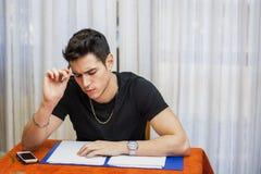 Όμορφος νεαρός άνδρας που μελετά ή που κάνει την εργασία Στοκ εικόνες με δικαίωμα ελεύθερης χρήσης