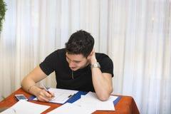 Όμορφος νεαρός άνδρας που μελετά ή που κάνει την εργασία Στοκ φωτογραφία με δικαίωμα ελεύθερης χρήσης