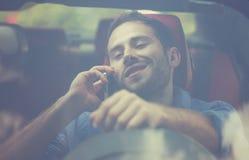 Όμορφος νεαρός άνδρας που μιλά στο κινητό τηλέφωνο οδηγώντας το αυτοκίνητό του Στοκ Φωτογραφίες