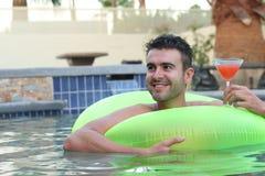 Όμορφος νεαρός άνδρας που πίνει ένα κοκτέιλ χαλαρώνοντας σε μια πισίνα Στοκ Φωτογραφία