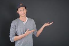 Όμορφος νεαρός άνδρας που παρουσιάζει με τα χέρια πριν από τον πίνακα Στοκ φωτογραφία με δικαίωμα ελεύθερης χρήσης