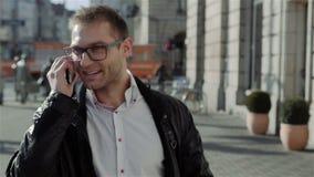 Όμορφος νεαρός άνδρας που περπατά και που μιλά στο τηλέφωνο, σε αργή κίνηση απόθεμα βίντεο