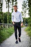 Όμορφος νεαρός άνδρας που περπατά στο πάρκο πόλεων Στοκ Εικόνα