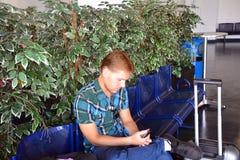 Όμορφος νεαρός άνδρας που ταξιδεύει και που εξετάζει το κινητό τηλέφωνό του Στοκ φωτογραφία με δικαίωμα ελεύθερης χρήσης