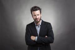 Όμορφος νεαρός άνδρας που φορά το γκρίζο κοστούμι Στοκ Εικόνες