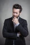 Όμορφος νεαρός άνδρας που φορά το γκρίζο κοστούμι Στοκ Φωτογραφία
