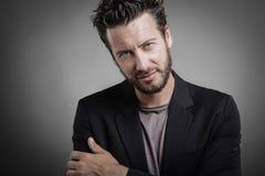 Όμορφος νεαρός άνδρας που φορά το γκρίζο κοστούμι Στοκ Φωτογραφίες