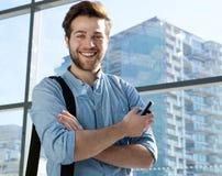 Όμορφος νεαρός άνδρας που χαμογελά με το κινητό τηλέφωνο Στοκ Εικόνες