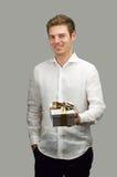Όμορφος νεαρός άνδρας που χαμογελά προσφέροντας το συμπαθητικό κιβώτιο δώρων Στοκ Φωτογραφία