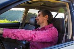Όμορφος νεαρός άνδρας σε ένα πουκάμισο που οδηγεί ένα αυτοκίνητο Στοκ Εικόνες