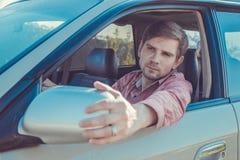 Όμορφος νεαρός άνδρας σε ένα πουκάμισο που οδηγεί ένα αυτοκίνητο Στοκ Φωτογραφίες