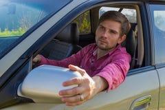 Όμορφος νεαρός άνδρας σε ένα πουκάμισο που οδηγεί ένα αυτοκίνητο Στοκ εικόνα με δικαίωμα ελεύθερης χρήσης