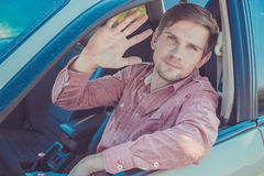 Όμορφος νεαρός άνδρας σε ένα πουκάμισο που οδηγεί ένα αυτοκίνητο Στοκ φωτογραφία με δικαίωμα ελεύθερης χρήσης