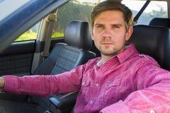 Όμορφος νεαρός άνδρας σε ένα πουκάμισο που οδηγεί ένα αυτοκίνητο Στοκ Φωτογραφία