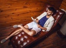 Όμορφος νεαρός άνδρας στην άσπρη χαλάρωση κοστουμιών στον καναπέ πολυτέλειας με το ημερολόγιο Στοκ φωτογραφίες με δικαίωμα ελεύθερης χρήσης