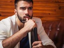 Όμορφος νεαρός άνδρας στην άσπρη χαλάρωση κοστουμιών στον καναπέ πολυτέλειας με το ημερολόγιο Στοκ Φωτογραφία