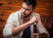 Όμορφος νεαρός άνδρας στην άσπρη χαλάρωση κοστουμιών στον καναπέ πολυτέλειας με το ημερολόγιο Στοκ Φωτογραφίες