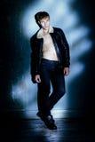 Όμορφος νεαρός άνδρας στη μαύρη τοποθέτηση σακακιών στο στούντιο Στοκ Φωτογραφία