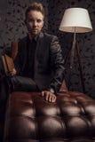 Όμορφος νεαρός άνδρας στη σκοτεινή χαλάρωση κοστουμιών στον καναπέ πολυτέλειας με το βιβλίο. Στοκ εικόνα με δικαίωμα ελεύθερης χρήσης