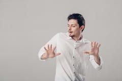 Όμορφος νεαρός άνδρας στο άσπρο πουκάμισο που χορεύει και που έχει τη διασκέδαση στο gre Στοκ Εικόνες