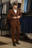 Όμορφος νεαρός άνδρας στο κλασικό κοστούμι Είναι στην αίθουσα εκθέσεως, που προσπαθεί στα ενδύματα, τοποθέτηση Διαφημιστική φωτογ Στοκ Φωτογραφία