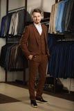 Όμορφος νεαρός άνδρας στο κλασικό κοστούμι Είναι στην αίθουσα εκθέσεως, που προσπαθεί στα ενδύματα, τοποθέτηση Διαφημιστική φωτογ Στοκ εικόνες με δικαίωμα ελεύθερης χρήσης