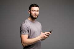 Όμορφος νεαρός άνδρας στο πουκάμισο που κρατά το κινητό τηλέφωνο και που εξετάζει τη κάμερα στεμένος στο γκρίζο κλίμα Στοκ εικόνες με δικαίωμα ελεύθερης χρήσης