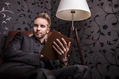 Όμορφος νεαρός άνδρας στο σκοτεινό κοστούμι με τη χαλάρωση βιβλίων στον καναπέ πολυτέλειας. Στοκ φωτογραφία με δικαίωμα ελεύθερης χρήσης