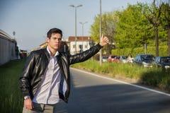 Όμορφος νεαρός άνδρας, hitchhiker που περιμένει στην άκρη του δρόμου Στοκ Φωτογραφία