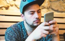 Όμορφος νεαρός άνδρας sms που χρησιμοποιώντας app στο smartphone Στοκ φωτογραφίες με δικαίωμα ελεύθερης χρήσης