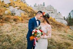 Όμορφος νεόνυμφος στο μοντέρνο μπλε κοστούμι που αγκαλιάζει την άσπρη ντυμένη ανθοδέσμη εκμετάλλευσης νυφών των τριαντάφυλλων στο Στοκ φωτογραφίες με δικαίωμα ελεύθερης χρήσης