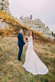 Όμορφος νεόνυμφος στο μοντέρνο μπλε κοστούμι που αγκαλιάζει την άσπρη ντυμένη ανθοδέσμη εκμετάλλευσης νυφών των τριαντάφυλλων στο Στοκ εικόνα με δικαίωμα ελεύθερης χρήσης