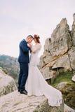 Όμορφος νεόνυμφος στο μοντέρνο μπλε κοστούμι που φιλά στοργικά τα άσπρα ντυμένα χέρια νυφών του στο μεγαλοπρεπές τοπίο βουνών με Στοκ φωτογραφία με δικαίωμα ελεύθερης χρήσης