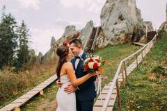 Όμορφος νεόνυμφος στο μοντέρνο μπλε κοστούμι που φιλά την άσπρη ντυμένη ανθοδέσμη εκμετάλλευσης νυφών τριαντάφυλλών του στο μεγαλ Στοκ Εικόνα