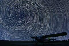Όμορφος νυχτερινός ουρανός, σπειροειδή ίχνη αστεριών πέρα από το μικρό αεροπλάνο αερολιμένων Στοκ Εικόνες