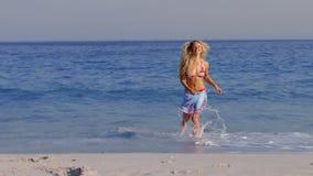 Όμορφος ξανθός έχοντας τη διασκέδαση στη θάλασσα απόθεμα βίντεο
