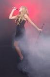 Όμορφος ξανθός αστέρας της ροκ στο σκηνικό τραγούδι Στοκ Φωτογραφίες