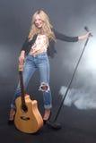Όμορφος ξανθός αστέρας της ροκ στο σκηνικό τραγούδι Στοκ Εικόνες