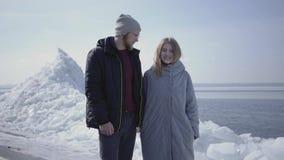 Όμορφος ξανθός γενειοφόρος άνδρας και ελκυστική νέα γυναίκα στα θερμά παλτά που κρατούν τα χέρια Καταπληκτική άποψη του χιονώδους φιλμ μικρού μήκους