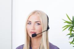 Όμορφος ξανθός, θηλυκός χειριστής εξυπηρέτησης πελατών που χρησιμοποιεί την κάσκα Στοκ Εικόνες
